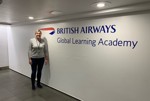 Woman standing in front of British Airways sign